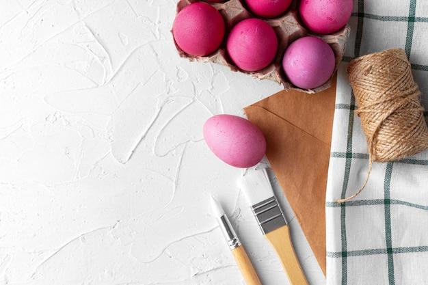 Peinture des oeufs de pâques en rose sur tableau blanc, vue de dessus