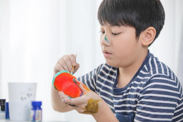 Peinture de peinture heureux garçon asiatique.