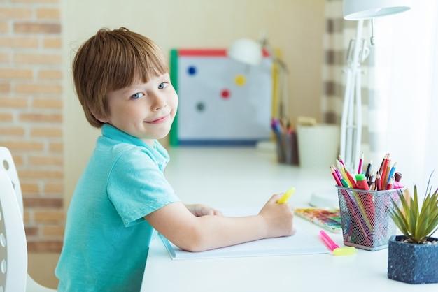 Peinture de petit garçon mignon avec des crayons de couleur à la maison