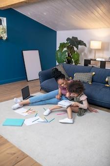 Peinture. petite fille afro-américaine avec une jeune mère dessinant avec des crayons de couleur assis sur le sol dans une pièce confortable à la maison