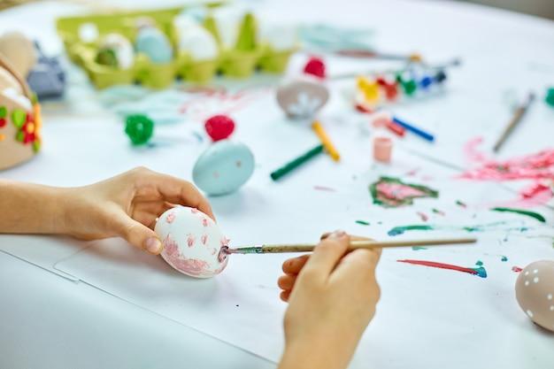 Peinture de petite fille méconnaissable, dessin avec des oeufs de pinceau à la maison. enfant se préparant pour pâques, s'amusant et célébrant la fête. joyeuses pâques, bricolage