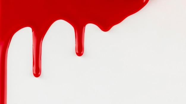 Peinture rouge dégoulinant sur fond blanc