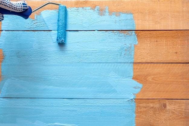 Peinture avec le rouleau de peinture de couleur bleue sur le bac de peinture verte sur le fond de bricolage en bois