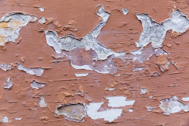 La peinture s'écaille sur un mur de béton brut