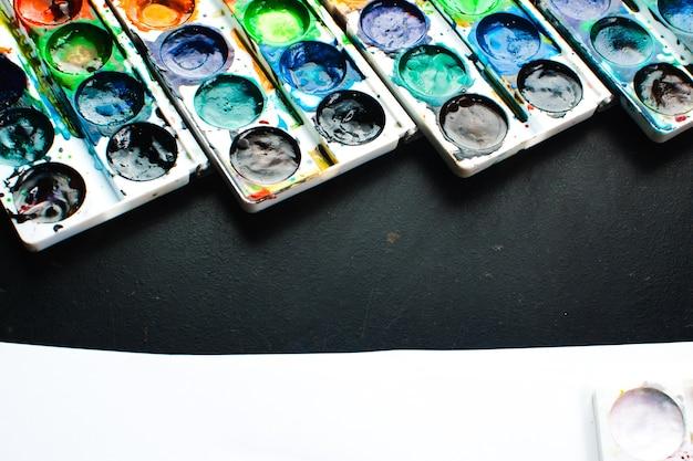 La peinture s'étend sur la surface noire, joli fond de lumières, créativité