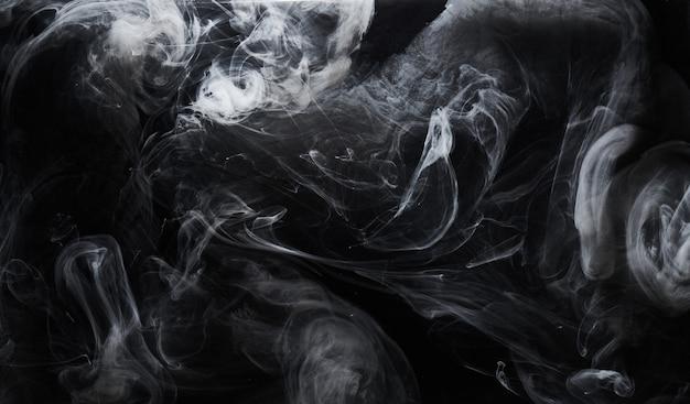 Peinture sombre abstraite sur fond d'eau. mouvement de nuage de fumée blanche sur des éclaboussures de tourbillon d'encre acrylique noire