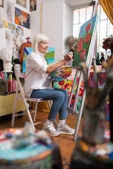 Peinture sur toile. femme âgée portant des jeans élégants et des baskets assis et peinture sur toile