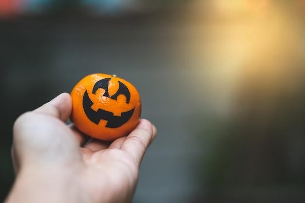 Une peinture de visage de citrouille oranges avec effrayant le jour de fête de halloween à portée de main