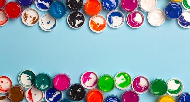 Des peintures acryliques de différentes couleurs pour le dessin sont ouvertes sur la table. fond coloré lumineux de pots de peinture