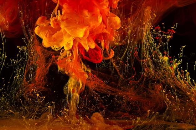 Les peintures acryliques et l'encre se déplacent dans l'eau sur fond noir