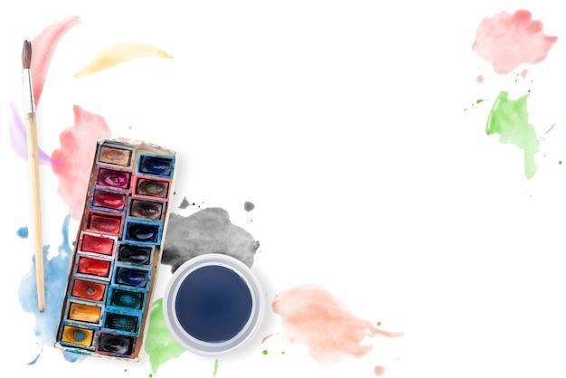 Peintures à l'aquarelle, pinceau et verre d'eau sur fond blanc avec des traits d'aquarelle.