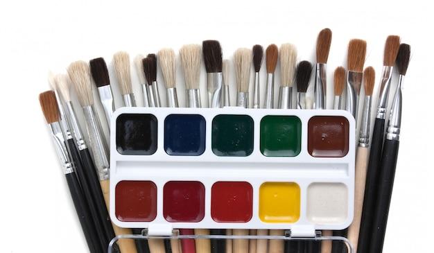 Peintures à l'aquarelle et pinceaux isolés sur fond blanc
