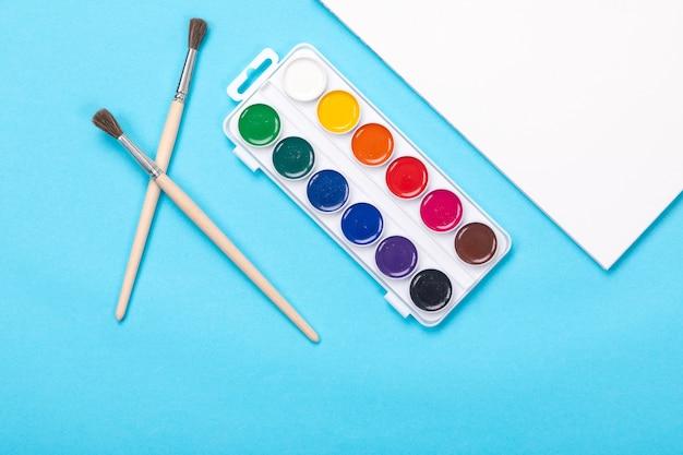 Peintures aquarelles et pinceau avec album pour peinture isolé sur bleu