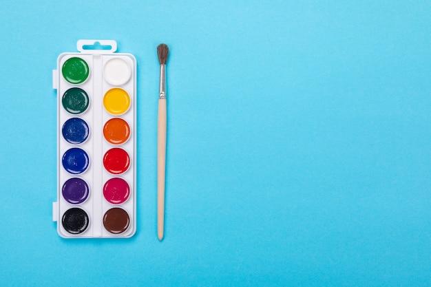 Peintures aquarelles et pinceau dans une boîte blanche, isolé sur bleu