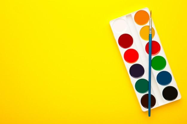 Peintures aquarelles avec pinceau sur fond jaune
