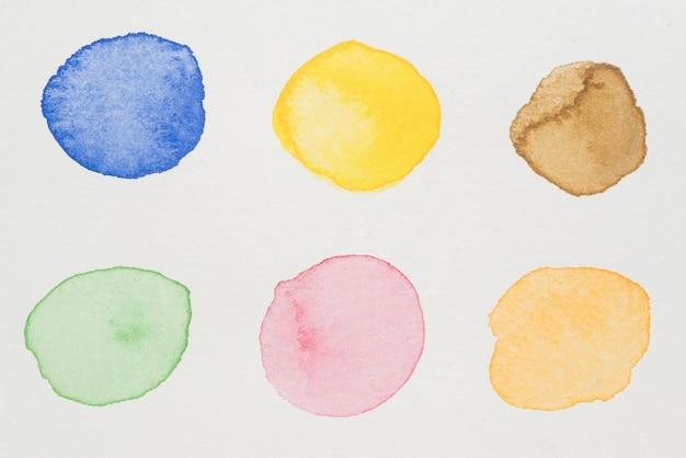 Peintures bleues, jaunes, marron, vertes, roses et orange sur papier blanc
