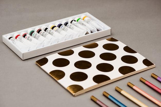Peintures à l'huile, crayons et carnet de croquis sur tableau gris