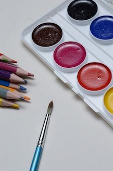 Peintures multicolores pour dessiner dans une palette, un pinceau et des crayons sur fond clair. fermer.