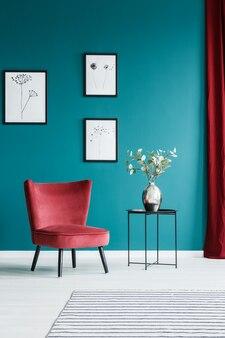 Peintures sur le mur vert à l'intérieur du salon avec fauteuil rouge et table d'appoint noire avec un vase à fleurs sur le dessus