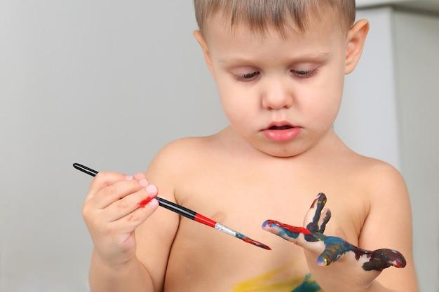 Les peintures de petit garçon peignent votre main