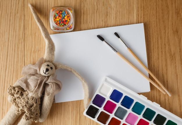 Peintures avec pinceau sur table avec poupée confortable en feutre