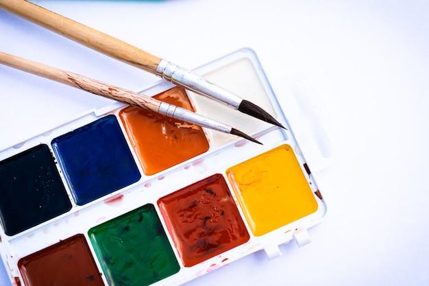 Peintures et pinceaux colorés sur fond blanc