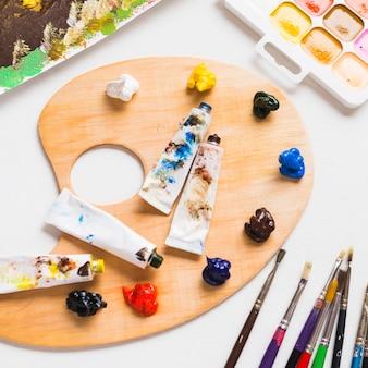 Peintures et pinceaux près de la palette en bois