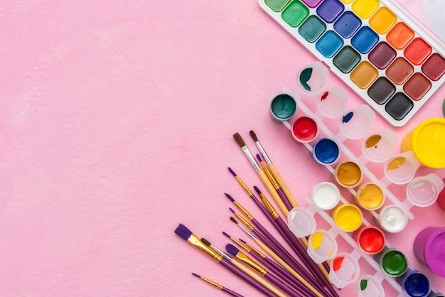 Peintures et pinceaux sur une surface rose