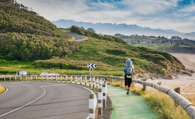 Pèlerin solitaire avec sac à dos marchant le camino de santiago en espagne, chemin de saint-jacques