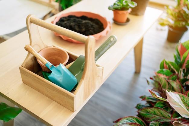 Pelle en aluminium colorée et pot de plante vide à l'intérieur d'un panier en bois sur la table avec préparation du sol.