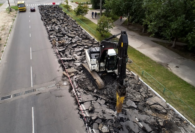 Pelle brisant la surface de la route en béton avec perceuse hydraulique pour réparer les travaux routiers.