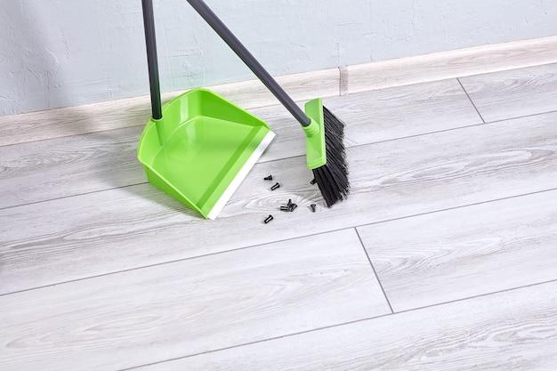 La pelle et la brosse en plastique nettoient le sol de la pièce de la poussière et des déchets.