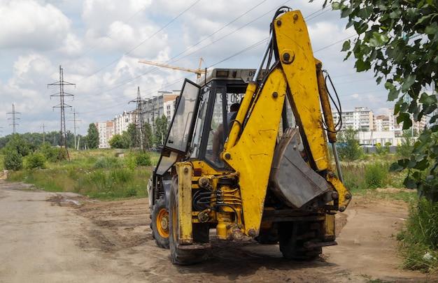 Pelle sur un chantier de construction sur fond de ciel. machinerie lourde au travail. un gros véhicule de construction jaune sur un chantier de construction. image industrielle.