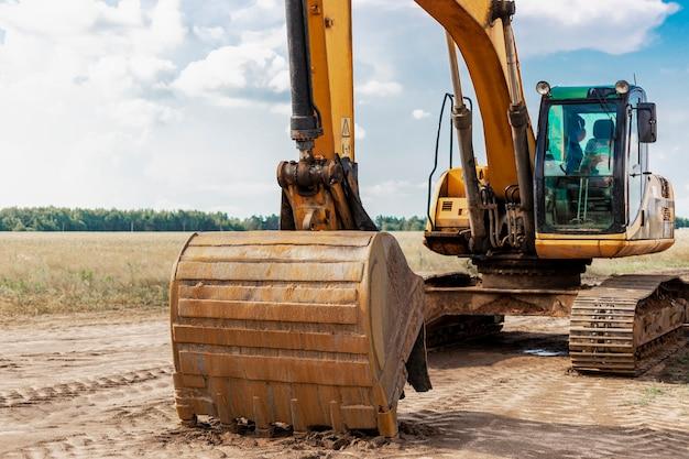 Une pelle sur chenilles lourde avec un grand godet se prépare pour le travail. matériel de construction lourd pour les travaux de terrassement. excavatrice de carrière. amélioration du territoire.