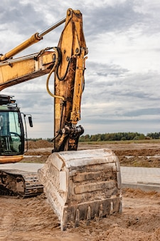 Pelle sur chenilles lourde avec un grand seau sur fond de ciel coucher de soleil. matériel de construction lourd pour les travaux de terrassement. amélioration du territoire.