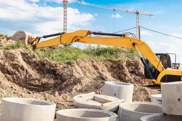 Une pelle creuse une fosse de fondation pour la construction d'un immeuble résidentiel. nouveaux bâtiments résidentiels en arrière-plan. fabrication de bâtiment. les fouilles.