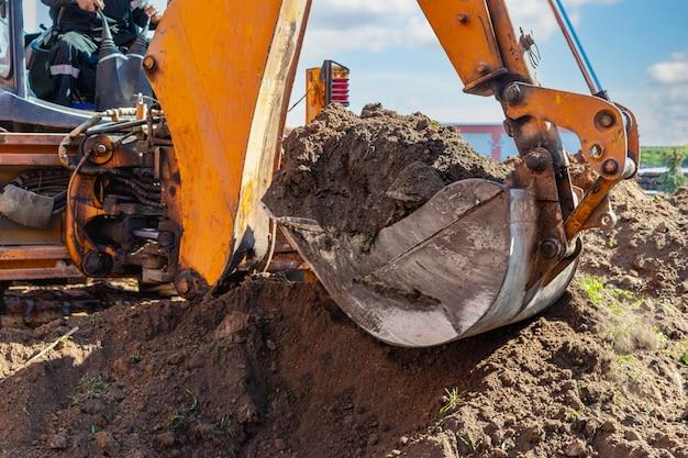 La pelle creuse une fosse de fondation profonde. fermer. travaux de terrassement sur un chantier de construction.