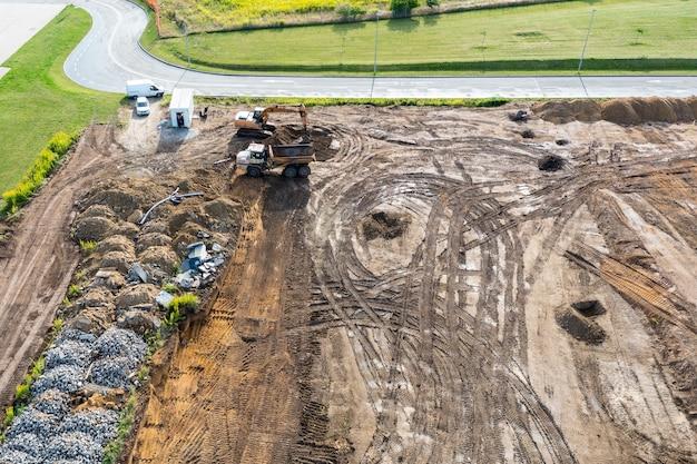 La pelle creuse une tranchée sous les fondations et le bulldozer nettoie le sol. vue de dessus d'un chantier de construction