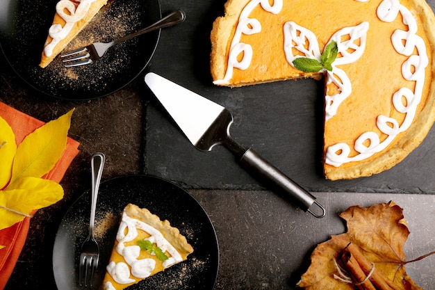 Pelle et délicieux gâteau à la citrouille avec décoration crème sur plaque d'ardoise