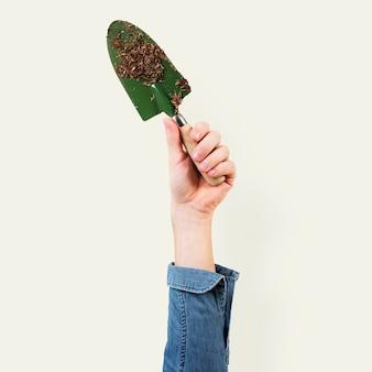 Pelle de jardinage tenue par la main d'une femme