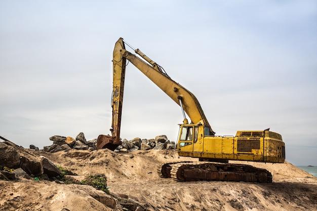 Pelle mashine travail avec du sable et des pierres. génie civil jaune