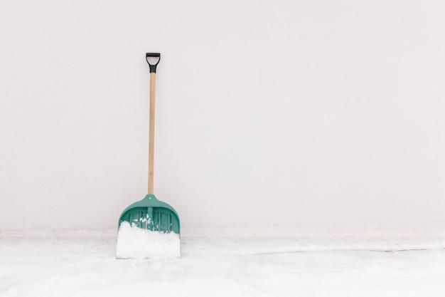 Une pelle à neige appuyée contre le mur blanc de la maison. photo de haute qualité