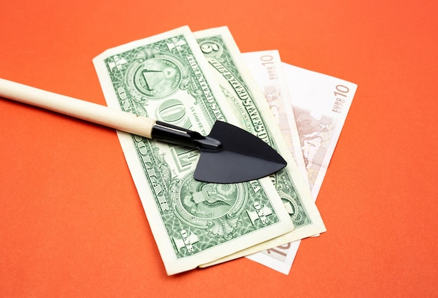 Pelle noire miniature avec gros plan de manche en bois sur fond orange avec des billets de banque
