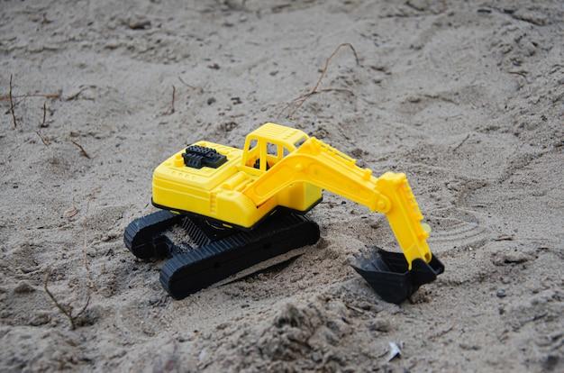 Pelle en plastique jaune dans le sable. matériel de construction de jouets. jouets pour enfants sur la plage.