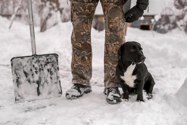 Une pelle pour déneiger se tient à côté des pieds d'un homme en bottes d'hiver