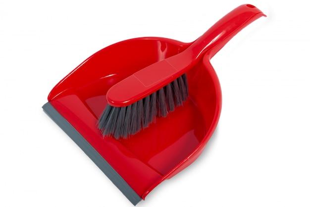 Pelle à poussière rouge et brosse isolé sur une surface blanche