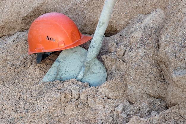 Une pelle recouverte de béton dans un tas de sable pour préparer le béton et un casque de travailleur de la construction orange.