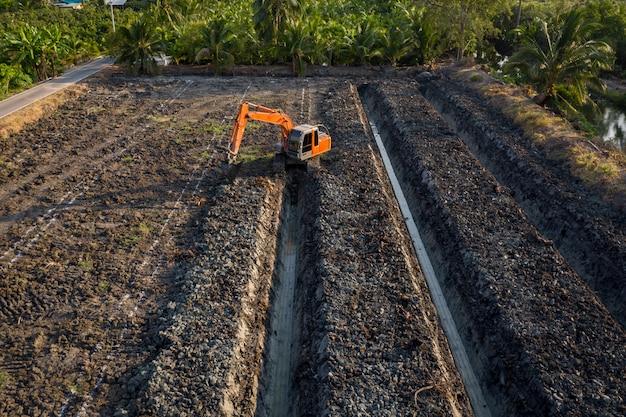 La pelle rétrocaveuse à angle élevé plonge dans la rainure du jardin et de l'agriculture thaïlande
