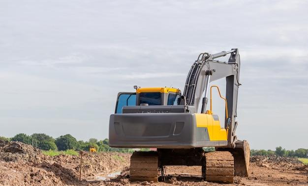 Pelle rétrocaveuse sur un chantier de construction pour le concept d'arrière-plan