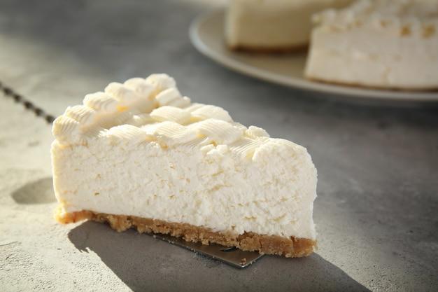 Pelle avec tranche de délicieux cheesecake sur table grise